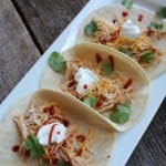 soft shelled chicken tacos with cilantro, sour cream, shredded cheddar cheese, and hot sauce sprinkled over the tacos. The taos are on a long, white platter on a barn wood board with a blue towel in the background.