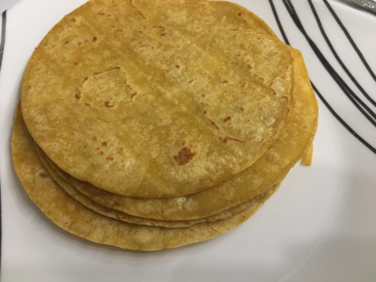 White plate with black stripes and golden brown soft corn tortillas on the plate.