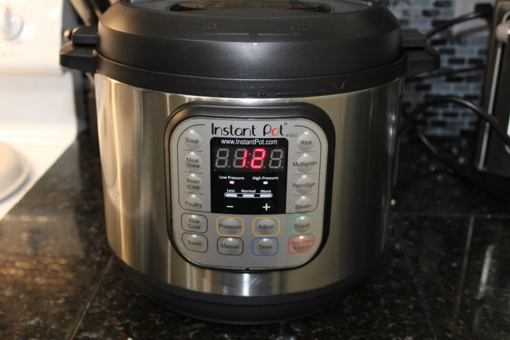 "A black and silver Instant Pot Duo sits on a black, granite kitchen counter top with the lid on and the cooking display read out lit up with the number ""12"" on it."