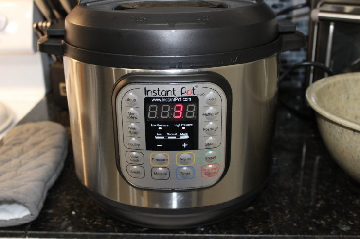 "A silver and black Instant Pot Duo is sitting on a black granite kitchen counter top with the lid on and the display showing the number ""3"". A brown mixing bowl is to the right of the Instant Pot and a grey oven mit is to the left of it. A white stove is barely visible on the left hand side and a black kitchen knife holder with silver kitchen knives is in the background along with a silver toaster oven."