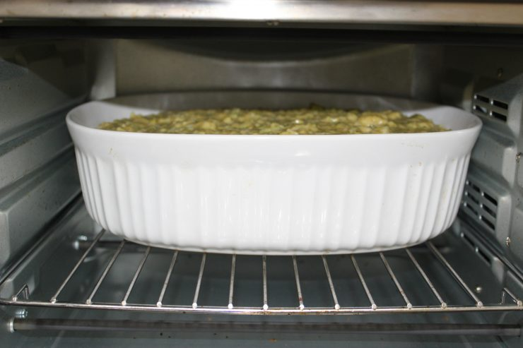 A white, oval, casserole dish filled with Broccoli Cheese Casserole has been placed inside a small, silver oven and is ready to cook. The oven door is open.