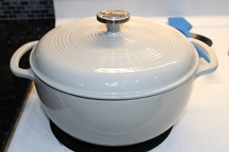 A large, white cast iron enameled Dutch Oven is sitting on a white stove top with the lid on.