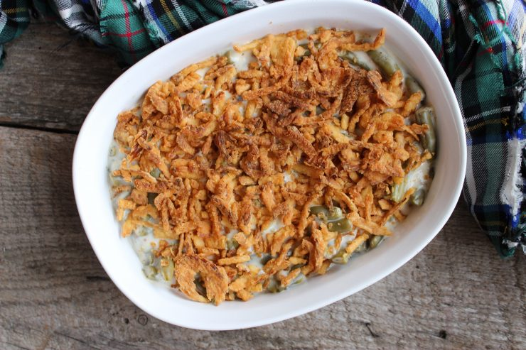 A full view overhead shot of Skinny Green Bean Casserole in a white, oval casserole dish. The casserole dish is sitting on a wooden board back drop with a green, red, white, and black plaid cloth behind the casserole dish and just visible.