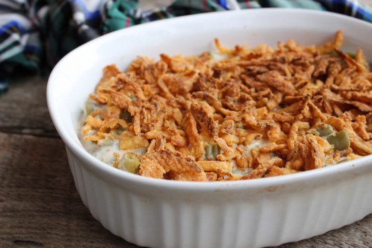 A white, oval casserole dish filled with Fresh Green Bean Casserole and sitting on a wooden back drop. A green, blue, white, and black plaid cloth is just visible in the background.