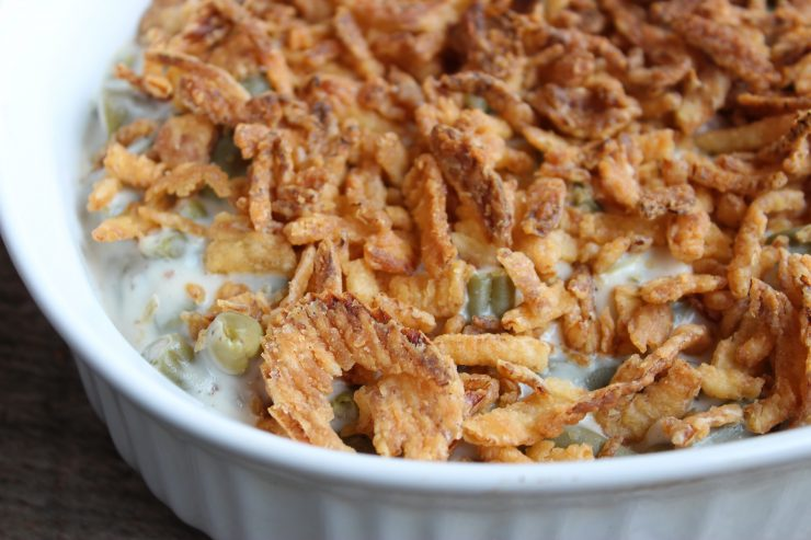 A close up, overhead shot of Skinny Green Bean Casserole that has been topped with crispy baked French Fried Onions. The Green Bean Casserole is in a white, oval casserole dish.