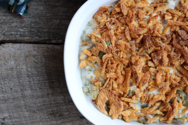 An overhead shot of a white, oval casserole dish filled with Skinny Green Bean Casserole and topped with French Fried Onions on a brown wood background.