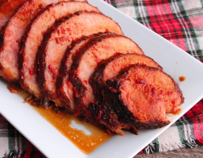 A large, white, rectangle platter is filled with a cascading line of red glazed and juicy Slow Cooker Holiday Ham cut into 1/4 inch thick slices. A red, white, black, and green tartan plaid fabric has been placed under the platter and is on a weathered wood back drop.