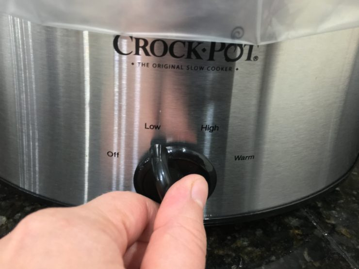 A white hand is adjusting the black knob on a silver and black Crock Pot Slow cooker to the low heat setting. The front of the slow cooker is the only thing visible, with a small portion of the plastic bag liner hanging down over the front of the slow cooker. The Crock Pot is sitting on a black, granite, counter top.