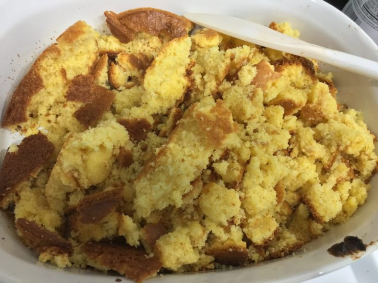 Cooked and crumbled, yellow, Jiffy Cornbread in a white, oval, 9x13 casserole dish. The casserole dish has a white mixing spoon resting in it in the upper right hand corner.