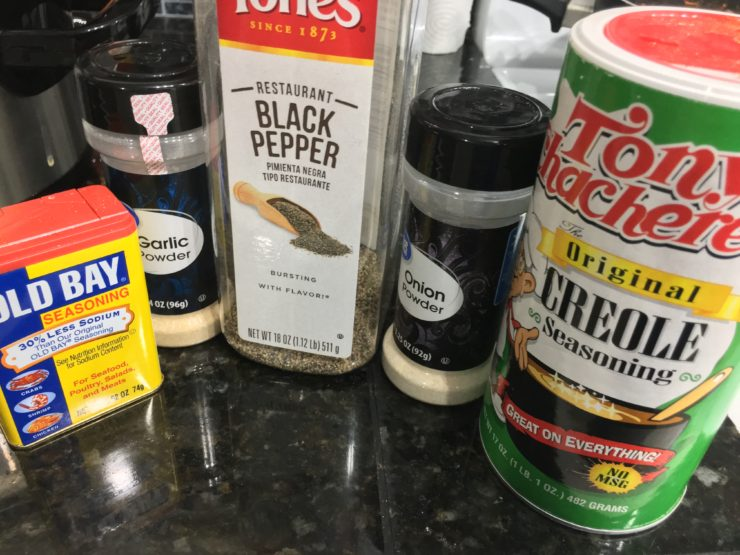 A container of Old Bay Seasoning, garlic powder, ground black pepper, onion powder, and Creole Seasoning sit on a black granite counter top with a white stove to the right of the photo.