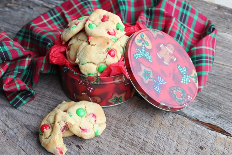 This photo is of a red, round, Christmas tin that has writing and gingerbread men all over it. The Christmas tin is filled with Easy M&M Christmas Cookies with the lid off and laying to the side. Three Christmas cookies, one with a bite taken out of it are sitting outside of the Christmas tin. Everything is sitting on a wooden backdrop and a red, green, and black tartan cloth is wrapped behind the Christmas tin.