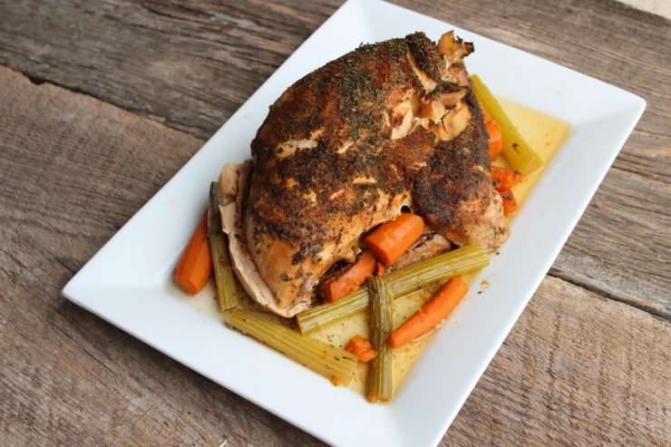 A large, white, rectangle platter with a whole roasted turkey breast that has been seasoned with cooked celery and carrot sticks around it on the platter. The platter is sitting on a brown wood weathered back drop.
