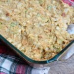 A 9x13 glass Pyrex casserole dish is filled to the brim with Granny's Southern Cornbread Dressing and pieces of white onion and green celery are visible throughout the golden yellow, baked dressing. A square portion of the Southern Cornbread Dressing is missing out of the upper corner, as if someone couldn't wait to get a bite. A red, white, black, and green tartan plaid cloth has been laid underneath the casserole dish and everything is sitting on a barn wood board back drop.