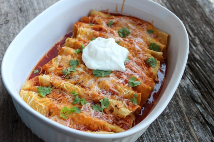 A white casserole dish sits in the center of a wooden backdrop and is filled with Skinny Chicken Enchiladas. The enchiladas are covered in shredded cheese and red enchilada sauce with a dollop of white, sour cream on top in the center. Flakes of green cilantro also covers the enchiladas.