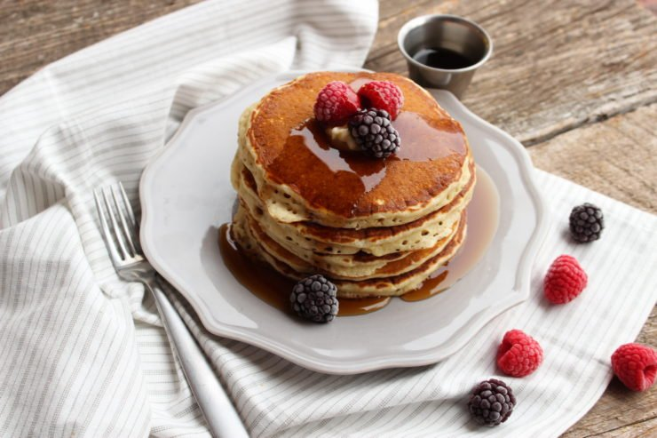 A stack of Easy Pancakes are sitting on a round, grey plate and topped with butter, syrup, blackberries, and raspberries. The plate is placed on a wooden backdrop with a white and grey striped towel underneath and a silver fork is placed to the left of the plate. A small silver up filled with syrup is sitting to the upper right of the plate. Blackberries and raspberries are scattered around the plate.