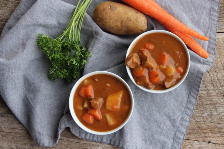 An overhead shot of Irish Beef Stew sits on a wooden back drop with a blue towel underneath. Two white bowls of Irish Beef Stew are placed beside a bunch of parsley, a russet potato, and two carrots.