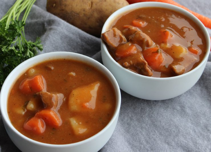 Two white bowls filled with Irish Beef Stew are placed on a blue towel. A bunch of parsley, a russet potato, and a carrot is visible behind the bowls of stew.