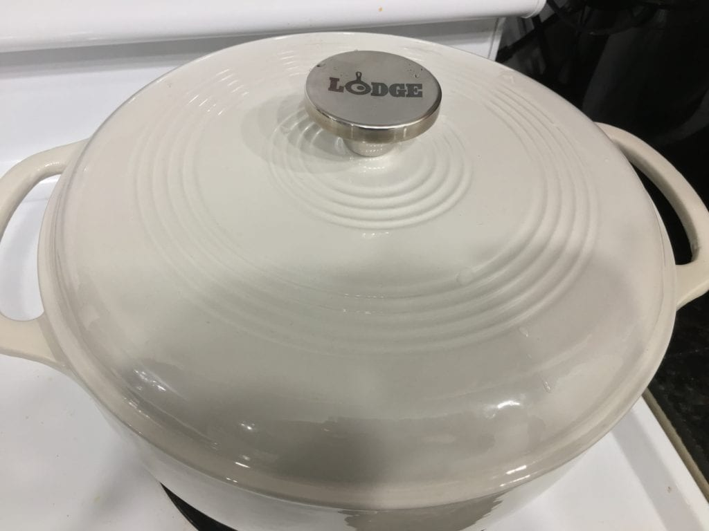 cream colored enameled Lodge cast iron dutch oven with lid on sitting on a white stove