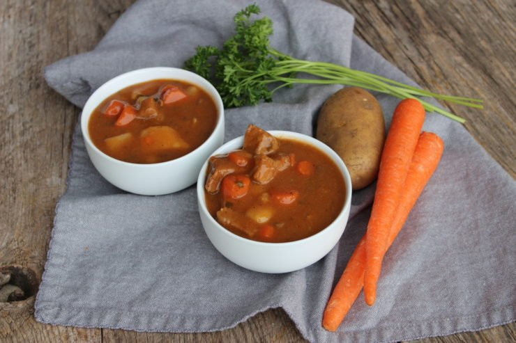 Two white bowls of Irish Beef Stew sits on a wooden backdrop with a blue towel underneath. Green parsley, a russet potato, and orange carrots sits behind the bowls.