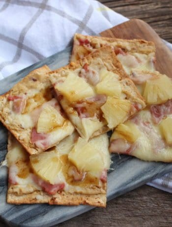 Slices of ham, pineapple, cheese, garlic hummus, and balsamic vinegar flat bread pizza on a gray marble and wood cheese board placed on a barn wood board with a white, gray, and yellow striped towel around the cheese board.