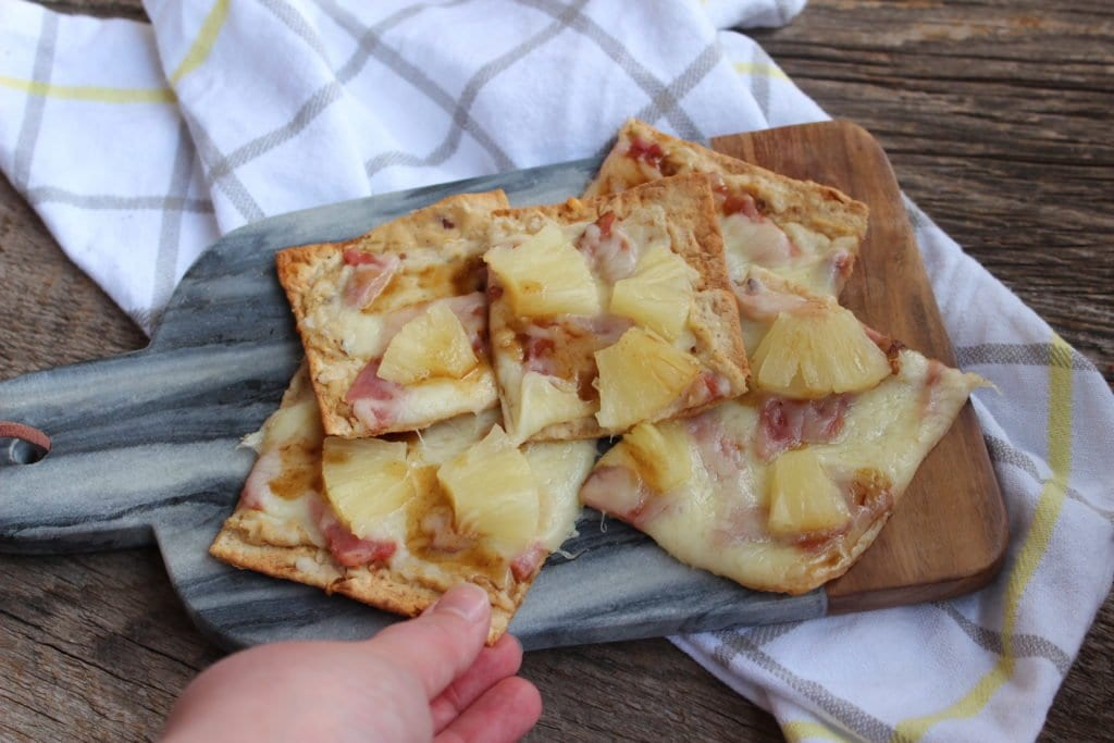Slices of ham, pineapple, cheese, garlic hummus, and balsamic vinegar flat bread pizza on a gray marble and wood cheese board placed on a barn wood board with a white, gray, and yellow striped towel around the cheese board with a left hand removing one piece of the pizza.