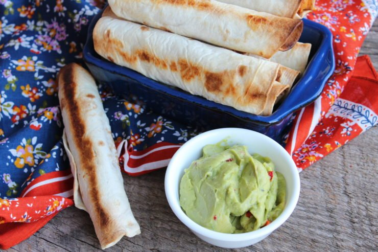 Flour taco shells baked with shredded chicken, cheese, and cream cheese inside, piled into a small, blue casserole dish. There is a small white, bowl of green guacamole placed beside the chicken taquitos and there is a multi-colored floral towel around the taquitos. Everything is sitting on a barn wood backdrop.