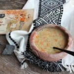 stone soup or soup from a stone made with carrots, onion, shallots, celery, parsley, basil, minced garlic, heavy whipping cream, water, chicken broth, chicken bullion, evaporated milk, seasoned salt, salt, and ground black pepper. Stone soup is in a handmade native american clay bowl with a black spoon. The clay bowl is sitting on a weathered wood board with a tasseled, aztec towel with a vintage copy of the book Stone Soup and a gray stone.
