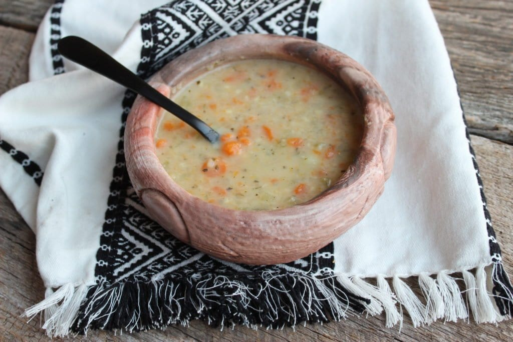 stone soup made from potatoes, carrots, celery, basil, parsley, water, chicken broth, chicken bullion, evaporated milk, heavy whipping cream, salt, ground black pepper, and seasoned salt. Stone soup is in a handmade, native american bowl with a black spoon. The bowl sits on a weathered barn wood board with an aztec design towel.