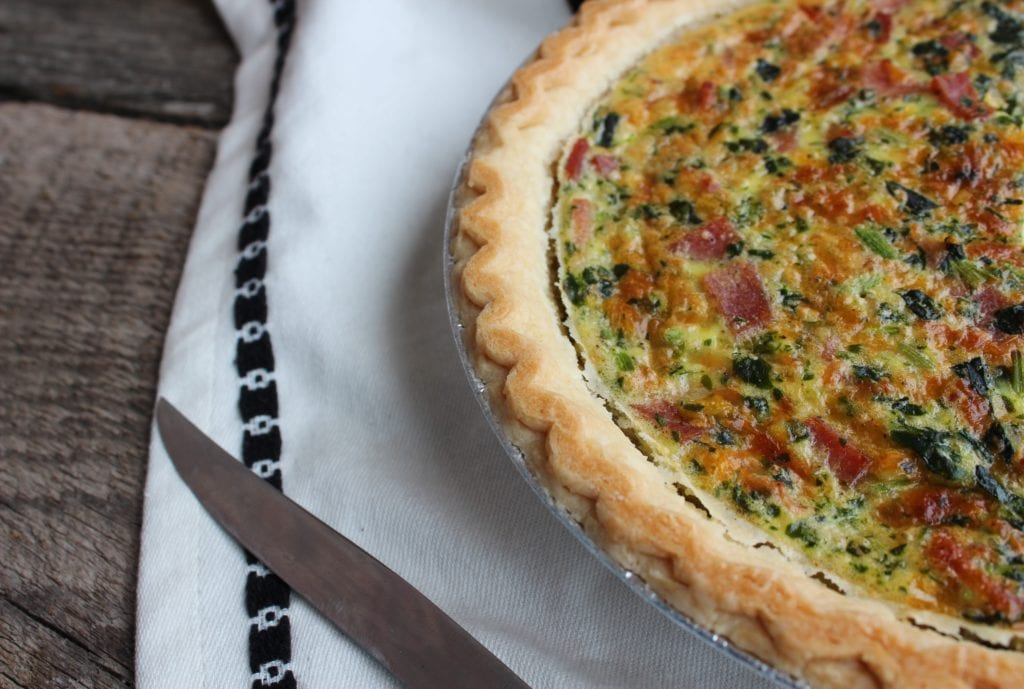 Cooked breakfast quiche in a silver pie pan sitting on a barn wood backdrop with a black and white Aztec tasseled towel underneath and a silver butter knife beside the quiche.