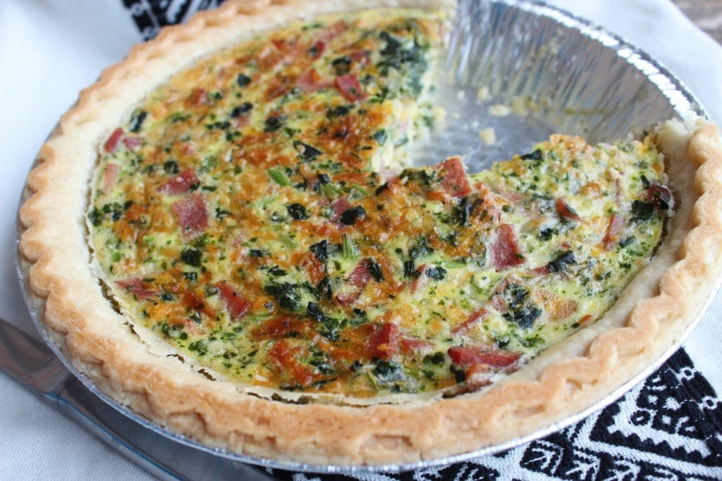 Ham, spinach, egg, and cheese quiche in a silver pie plate sitting on a black and white Aztec towel with one slice missing from the quiche.