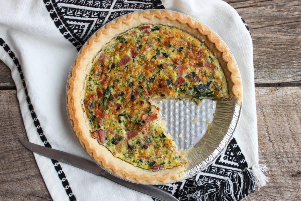 Cooked quiche in a silver pie pan placed on a barn wood board back drop with a black and white Aztec tasseled towel with a silver butter knife placed beside the quiche.