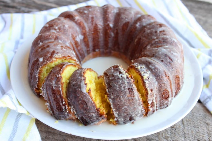 lemon pound cake with a lemon glaze on a white plate that's on a barn wood back drop with a white towel that has gray and yellow stripes.