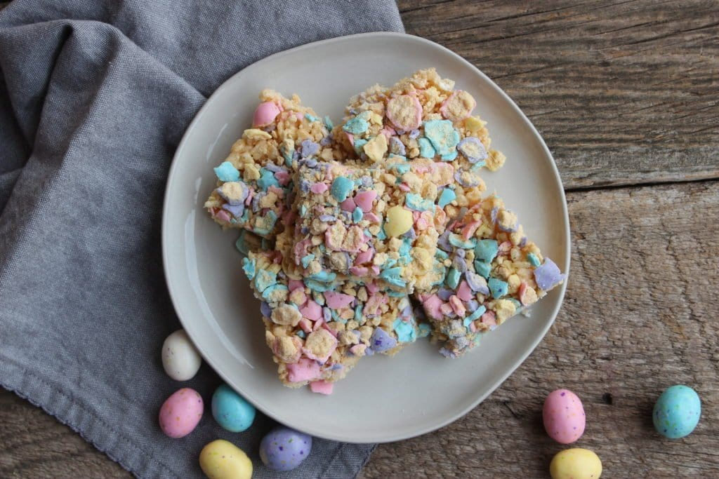Round white plate with rice krispie treats on the plate that have been topped with crushed, Mighty Malted, Malted Easter milk eggs, with malted milk eggs around the plate and a blue towel. The plate and towel is placed on a barn wood board backdrop.