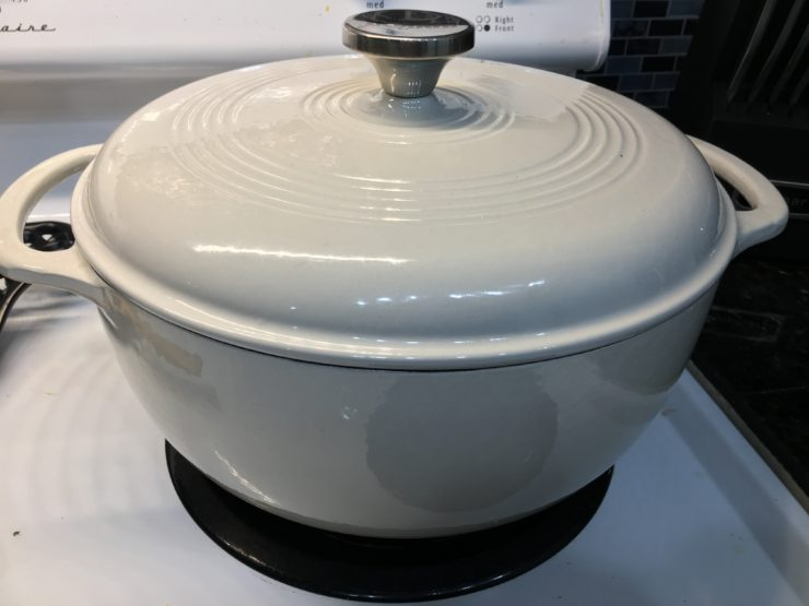 A white dutch oven sits on a white stove top with the lid on.