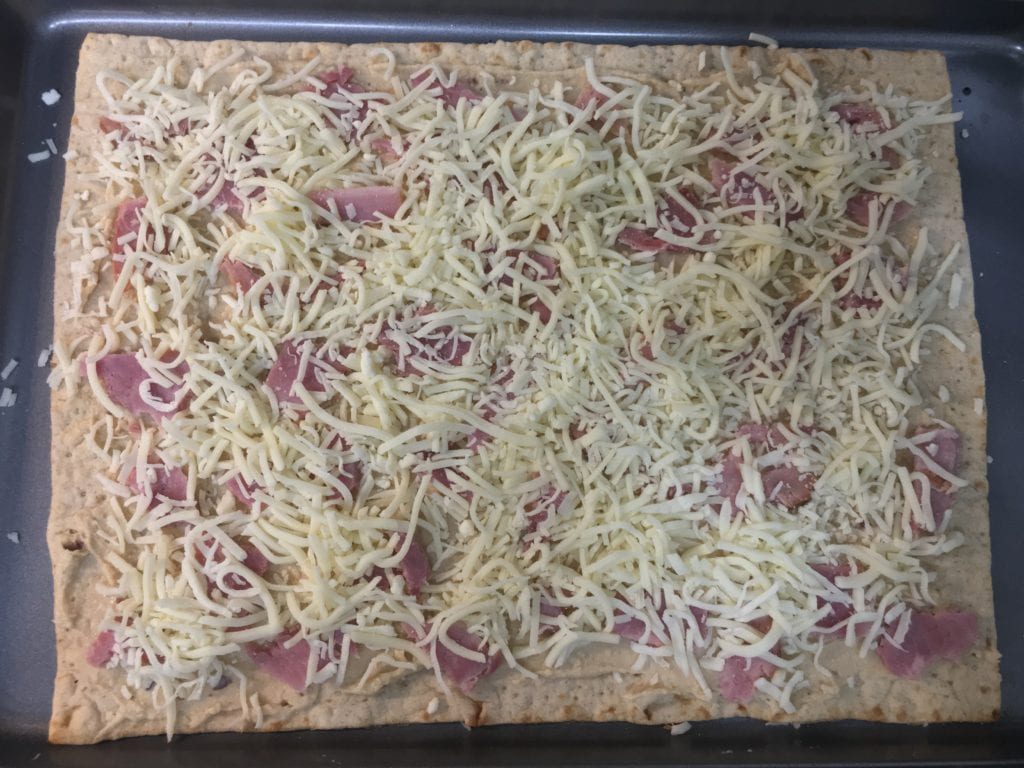 Lavish flat bread with garlic roasted hummus spread over it with diced ham and shredded mozzarella cheese sprinkled over it, all on a large, sheet pan.