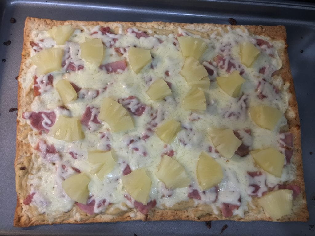 Cooked, flat bread pizza with roasted garlic hummus, melted shredded mozzarella cheese, diced ham, and diced pineapple on a large, flat, baking sheet.