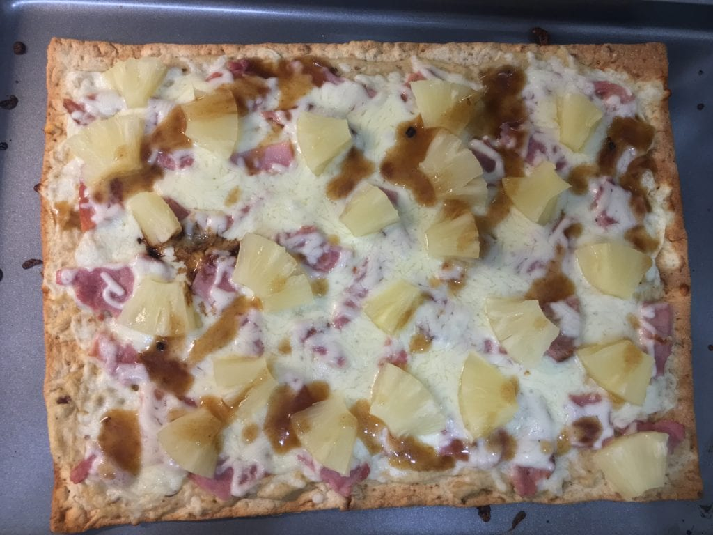 Cooked flat bread pizza with shredded, melted, mozzarella cheese, diced ham, diced pineapple, roasted garlic hummus, and drizzled balsamic vinegar.