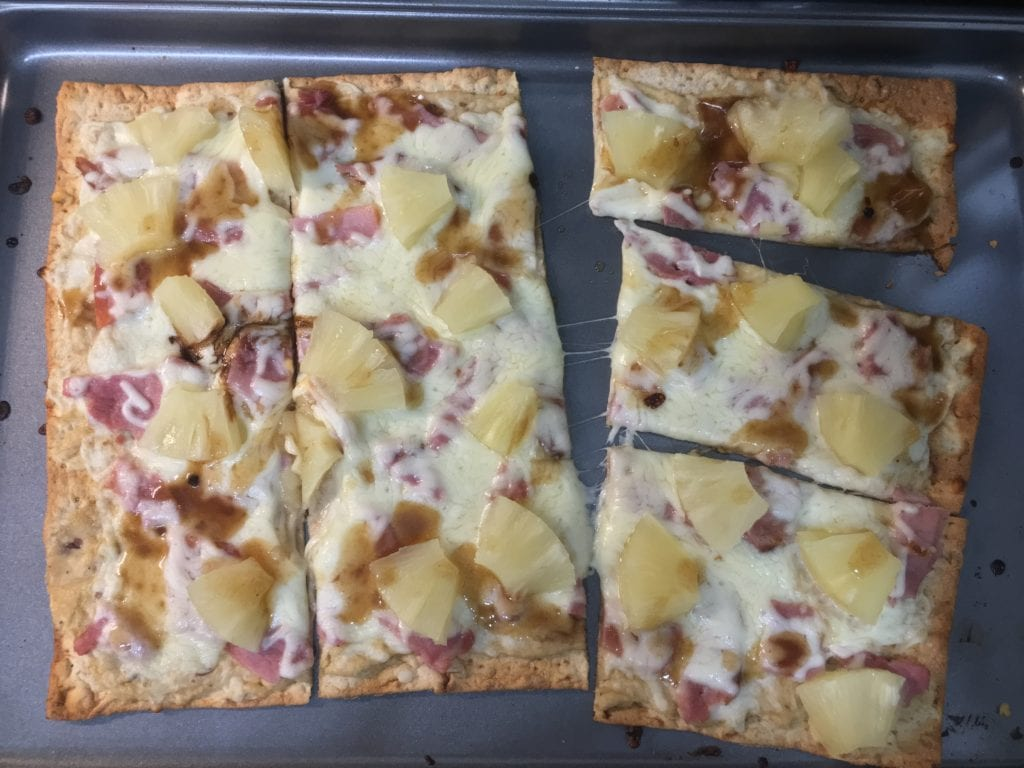 Cooked and sliced flat bread pizza with diced ham, diced pineapple, shredded, melted, mozzarella cheese, garlic hummus, and balsamic vinegar drizzled over.