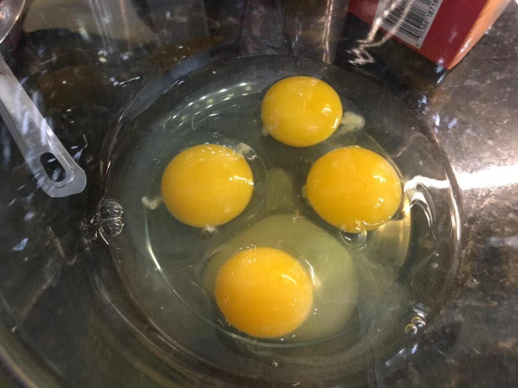 Four cracked eggs in a clear glass bowl sitting on a black, granite counter top.