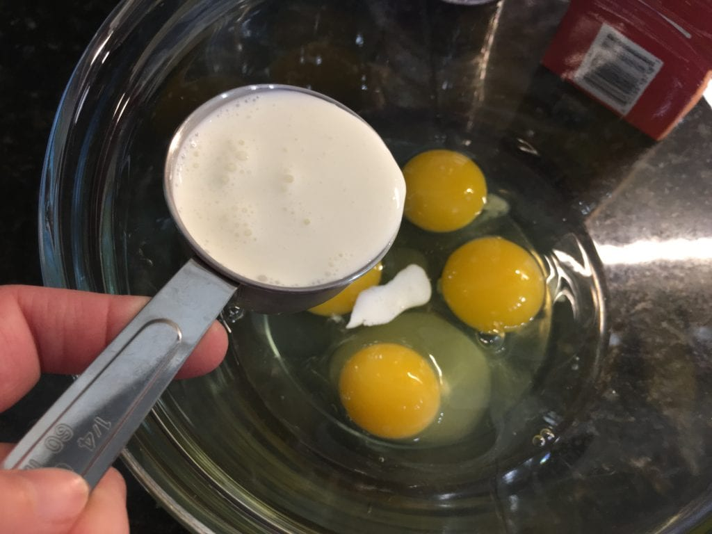 Four cracked eggs in a clear glass bowl with a silver measure cup shown over the bowl and white, heavy whipping cream in the cup.