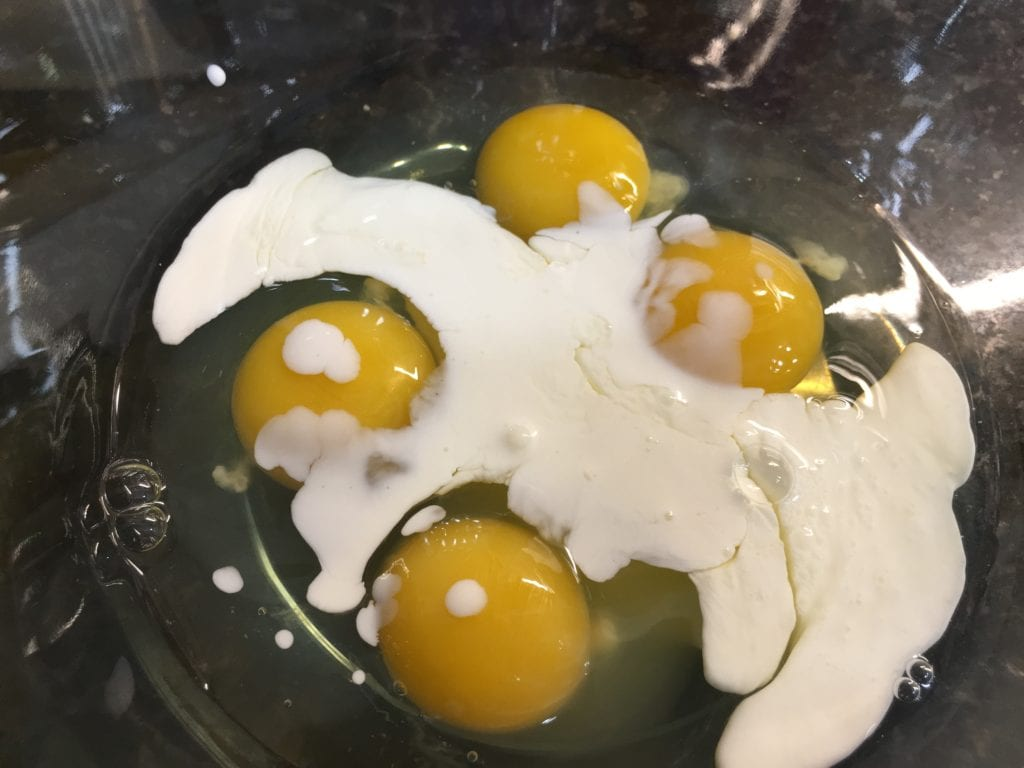 Four cracked raw eggs in a clear, glass bowl with one fourth of a cup of heavy whipping cream in with the eggs.