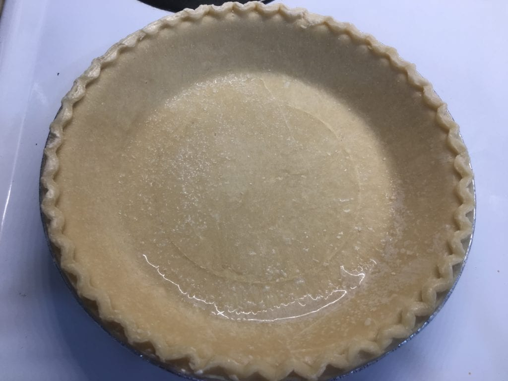Unbaked pie shell in a silver pie pan sitting on a white stove.