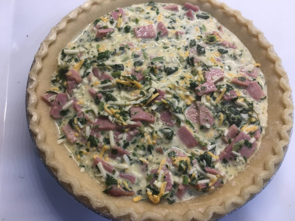 Ham, egg, spinach, and cheese quiche in a pie shell sitting on top of a white stove. Quiche is uncooked.