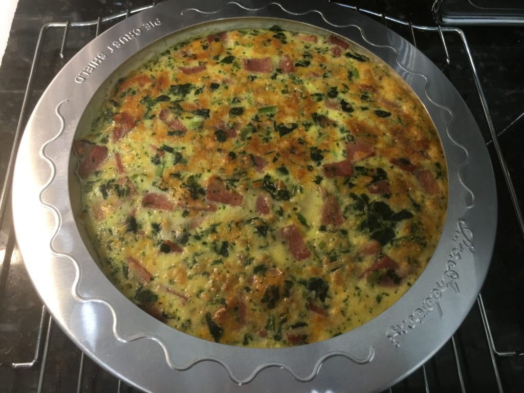 Cooked quiche sitting on a cooling rack with a silver pie crust saver over the top of the pie shell.