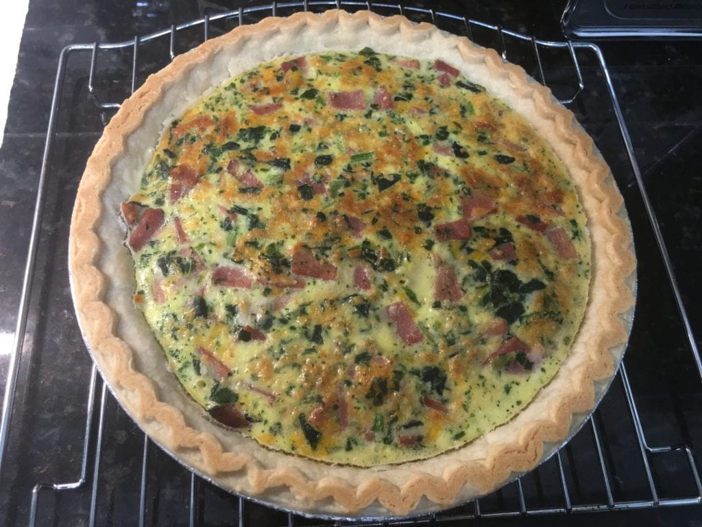 Cooked quiche sitting on a cooling rack on a black, granite counter top.
