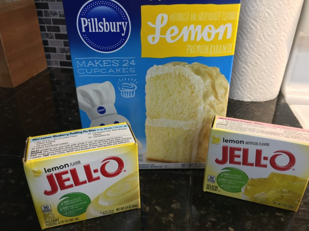 One Pillsbury Lemon Cake Mix box, on Jello Lemon Instant Pudding box, and one Jello Lemon Gelatin box sitting on a black, granite counter top.