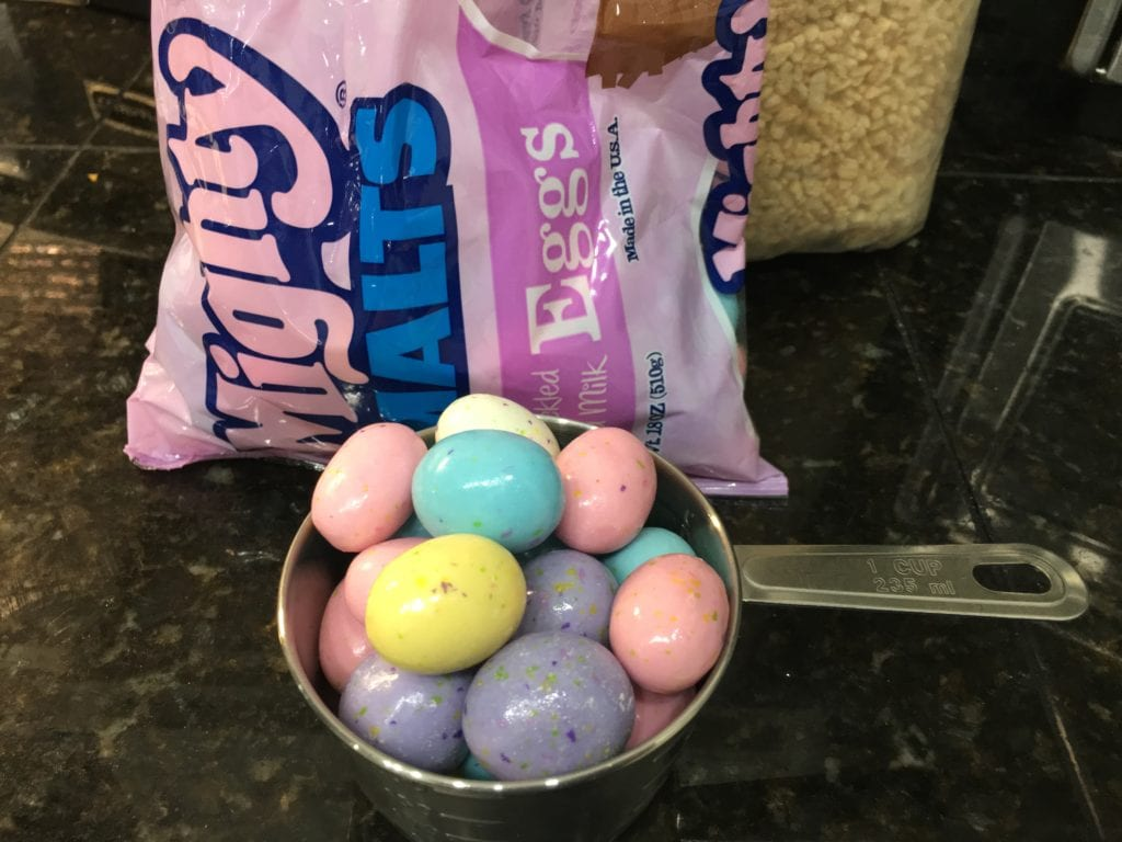 One large bag of Mighty Malts malted Easter milk eggs on a black granite counter top with a silver one cup measuring cup placed in front of the bag and the silver measuring cup is filled with pastel colored malted milk eggs.