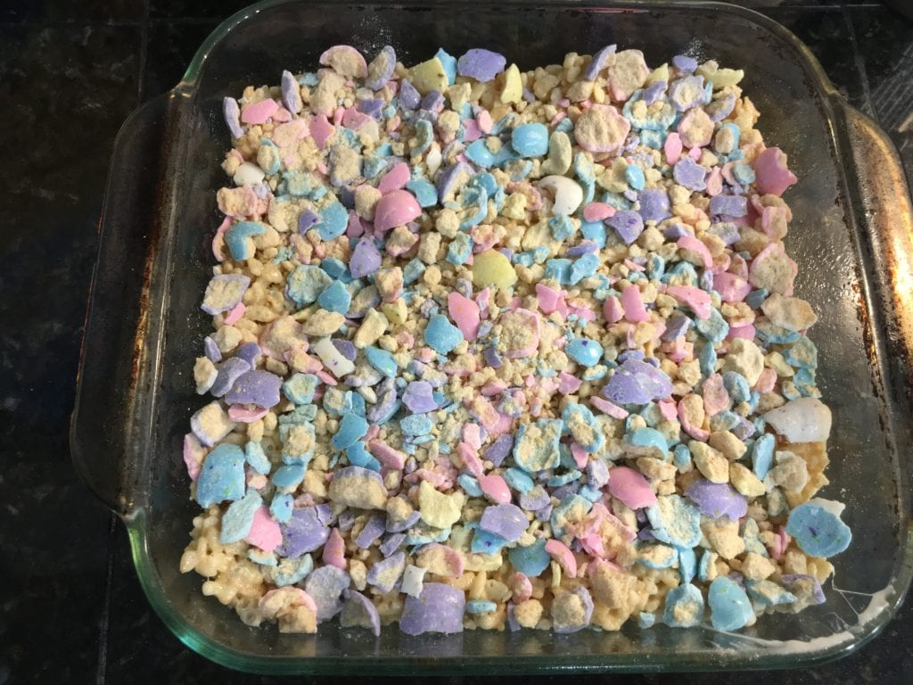 Rice krispies treats in a square, glass, 8x8 casserole pan with crushed, Mighty Malts Easter egg malted milk balls over the top of the rice krispies.