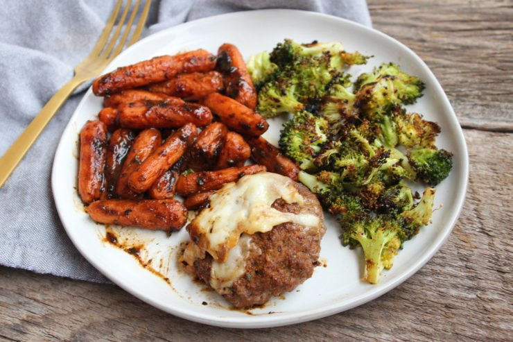 A white plate with a cheesy hamburger patty, roasted carrots, and roasted broccoli. A gold fork is placed beside the plate along with a blue towel.