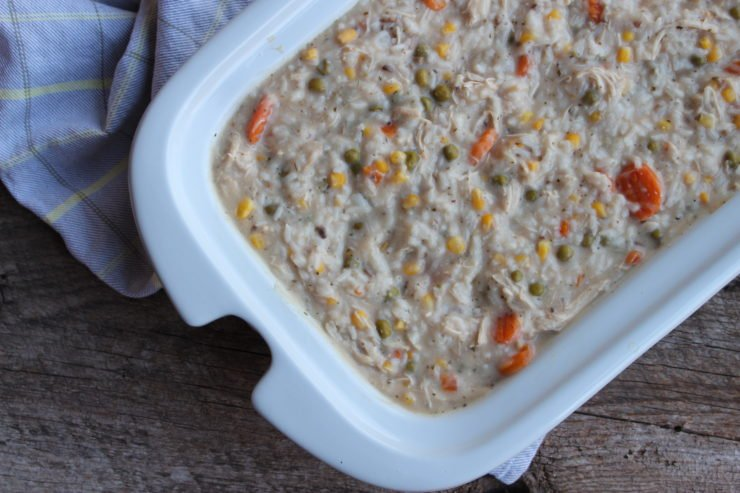 A white casserole dish with Slow Cooker Ranch Chicken and Veggie Casserole in the casserole dish with a gray, yellow striped towel beside the casserole dish.